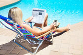The woman reading newspaper near the pool — Stock Photo