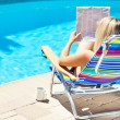 The woman is sitting near the pool — Stock Photo