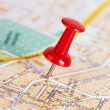 Red pushpin on a map - Stock Photo