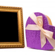 Gold frame and gift box on a white background — Stock Photo