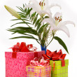 Beautiful bouquet of white lilies and present boxes on a white b — Stock Photo