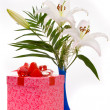 Beautiful bouquet of white lilies and present box on a white bac — Stock Photo