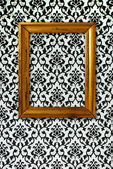 Gold frame on a black and white wallpaper — Stock Photo