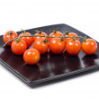 Cherry tomatoes in a black plate — Stock Photo