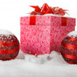 Christmas gift box in the snow with red balls and candles — Stock Photo