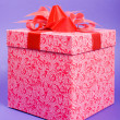 Single pink gift box with red ribbon on blue background. — Stock Photo