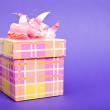 Single yellow gift box with pink ribbon on blue background. — Stock Photo #7841776