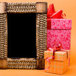 Photo frame and gift box with ribbon on orange background. — Стоковая фотография