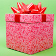 Single pink gift box with red ribbon on green background. — ストック写真