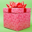 Single pink gift box with red ribbon on green background. — Foto Stock