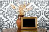 Golden photo frame and jug with wheat and flax on vintage table — Foto de Stock