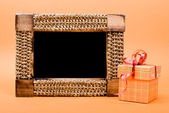 Photo frame and gift box with ribbon on yellow background. — Stock Photo