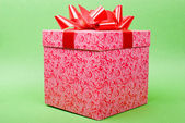 Single pink gift box with red ribbon on green background. — Stock Photo