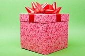 één roze geschenkdoos met rood lint op groene achtergrond. — Stockfoto
