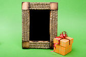 Photo frame and gift box with ribbon on green background. — Stock Photo