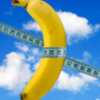 Banana with measure tape on sky background — Stock Photo #7114210