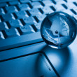 Stock Photo: Transparent globe on laptop keyboard