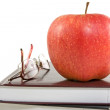 Royalty-Free Stock Photo: Red apple and glasses on the books
