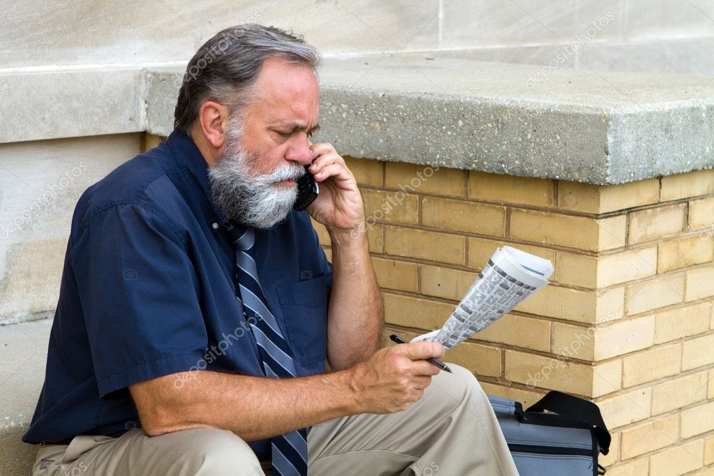 Mature unemployed salesman makes a call on his cell phone to reply to a advertisement for a want ad job in the newspaper.  Stock Photo #7296168