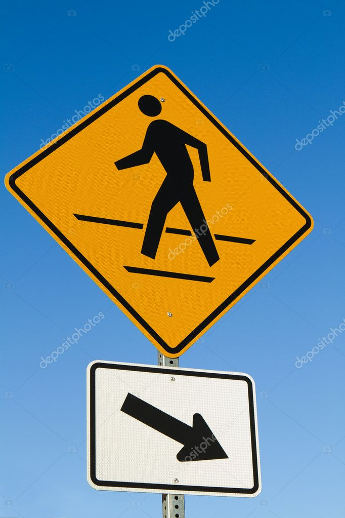 Pedestrians crosswalk sign with arrow against a blue sky. — Stock Photo #7785744