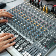 Stock Photo: Female hands at audio control console