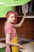 Vrouw in keuken interieur met schone platen — Stockfoto