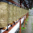 Buddhist monk and prayer wheels in a row — Stock Photo