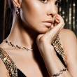 Elegant fashionable woman with golden jewelry — Stock Photo