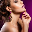 Elegant fashionable woman with violet jewelry — Stock Photo