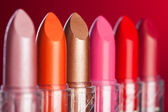 Many lipsticks on red background (shallow DOF) — Stock Photo