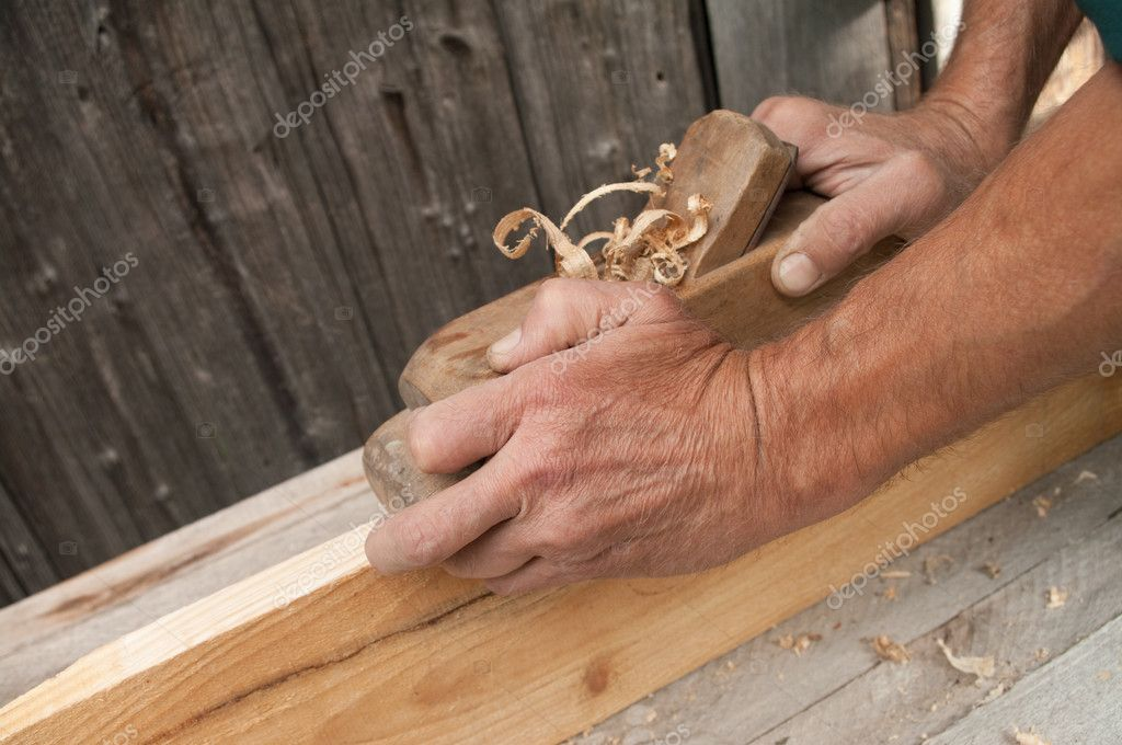 Hands of a carpenter planed wood, workplace  — Stock Photo #6982505