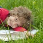 Beautiful little girl reads book — Stock Photo