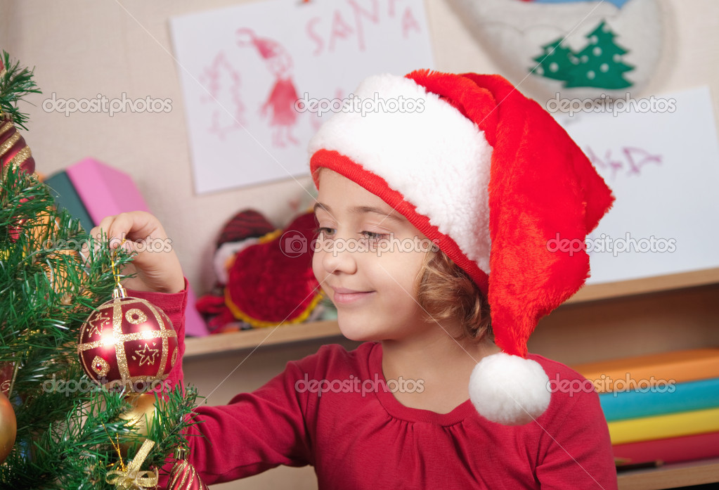 Little girl in the hat of Santa Claus decorates a Christmas tree — Foto Stock #7274095