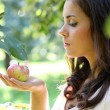 Cute young woman holding an apple in her hands against the backg — Stock Photo #6949796