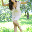 Stock Photo: Beautiful young woman dancing in the morning bright summer orchard