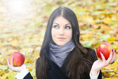 Portrait of the dreaming gorgeous woman hesitated with two bright fresh red — Stock Photo