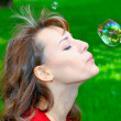 Portrait of stunning girl infleting soap bubbles - Stock Photo
