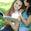 Beautiful mother and daughter reading fairy book in summer park — Stock Photo #6961300
