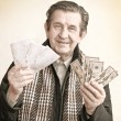 Photo: Elderly happy man with pack of money