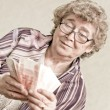 Elderly happy woman with pack of money — Stock Photo