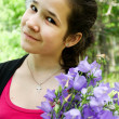 Happy young girl with brigth bluebell flowers in beautiful bunch — Stock Photo
