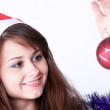 Attractive young girl with christmas presents wondering — Stock Photo #6963332