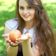 Brunette young girl with an apple in summer park enjoying — Stock Photo #6963584