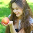 Brunette young girl with an apple in summer park enjoying — Stock Photo #6963586