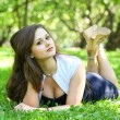 Sensual young brunette girl lying in summer park — Stock Photo #6963589
