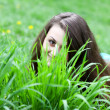 Stock Photo: Pretty young smiling girl concealing herself behind bright green blades of
