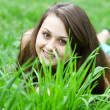 Pretty young cheerful girl concealing herself behind bright gree - Foto de Stock