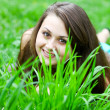 Stock Photo: Pretty young cheerful girl concealing herself behind bright gree