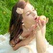 Brunette young girl with an apple in summer park enjoying — Stok fotoğraf