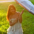 The young beautiful woman with white umbrella - Stock Photo